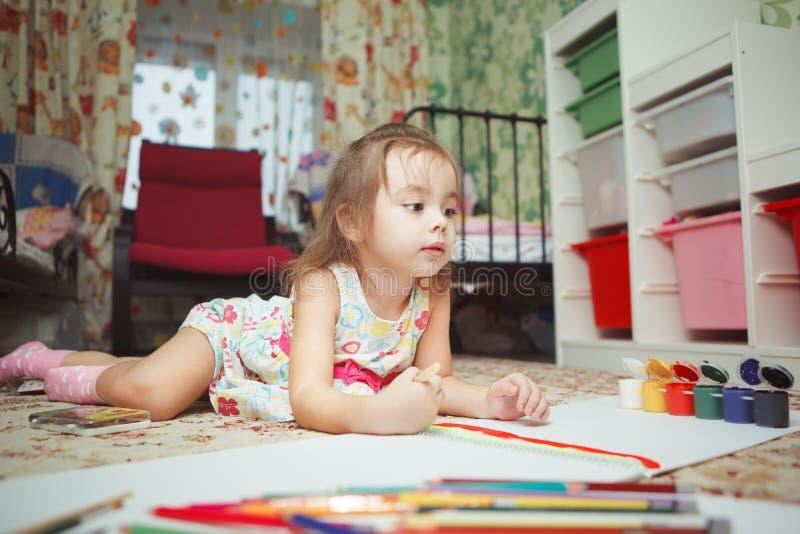 Het meisje ligt op slaapkamervloer en verfbeeld royalty-vrije stock foto