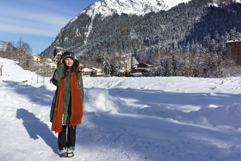 Het meisje loopt door het snow-covered dorp van Dombay in de Republiek karachay-Cherkess stock afbeelding