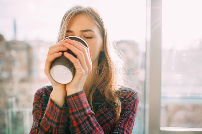 Het meisje loopt onderaan de straat met een document Kop van koffie, close-up, goed weer, vrouw in jasje, stock afbeeldingen