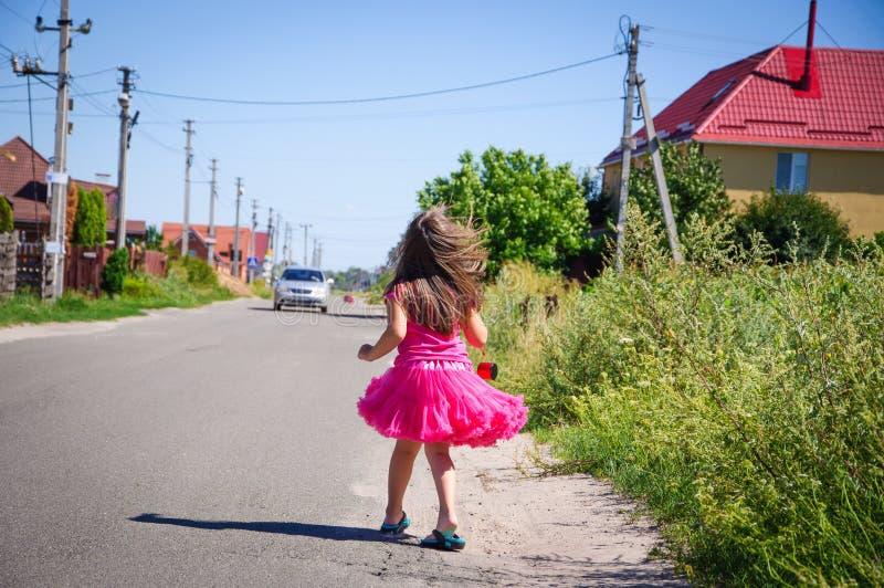 Download Het Meisje Loopt Op De Weg In Het Dorp Stock Afbeelding - Afbeelding bestaande uit gras, geluk: 107705177