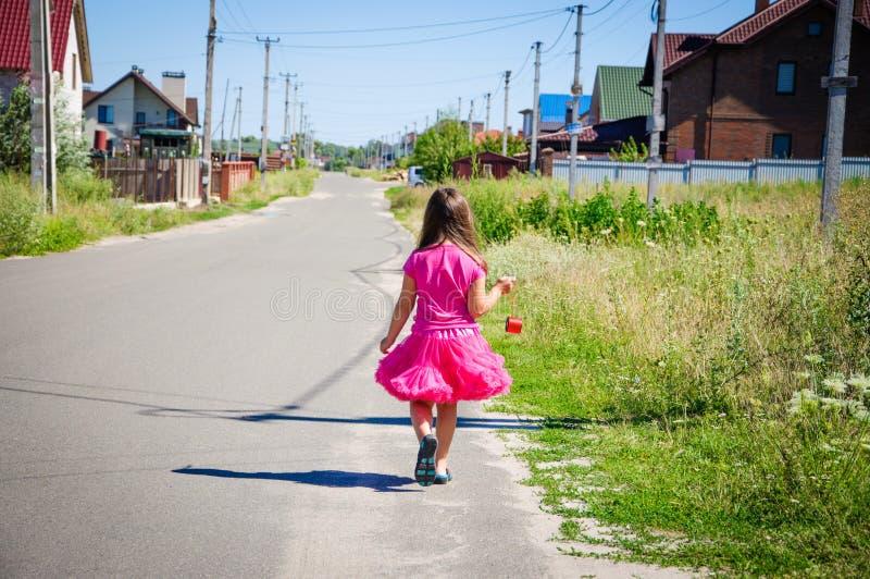 Download Het Meisje Loopt Op De Weg In Het Dorp Stock Foto - Afbeelding bestaande uit helder, gras: 107705450