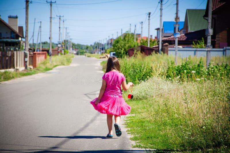 Download Het Meisje Loopt Op De Weg In Het Dorp Stock Afbeelding - Afbeelding bestaande uit vrolijk, blauw: 107705455