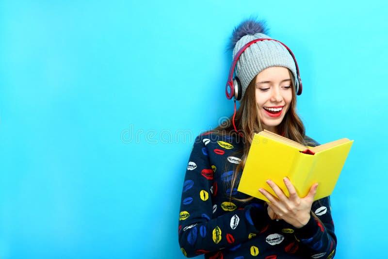 Het meisje luistert aan muziek en houdt een boek stock afbeeldingen
