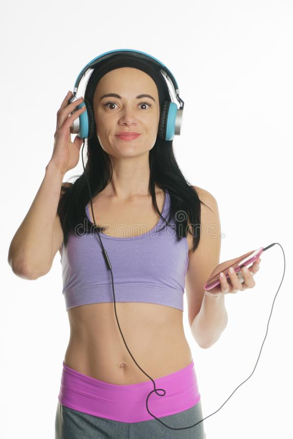 Het meisje luistert aan muziek hoofdtelefoons sportenmeisje in hoofdtelefoons stock foto's