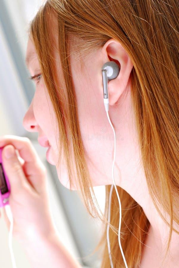 Het meisje luistert muziek royalty-vrije stock afbeeldingen