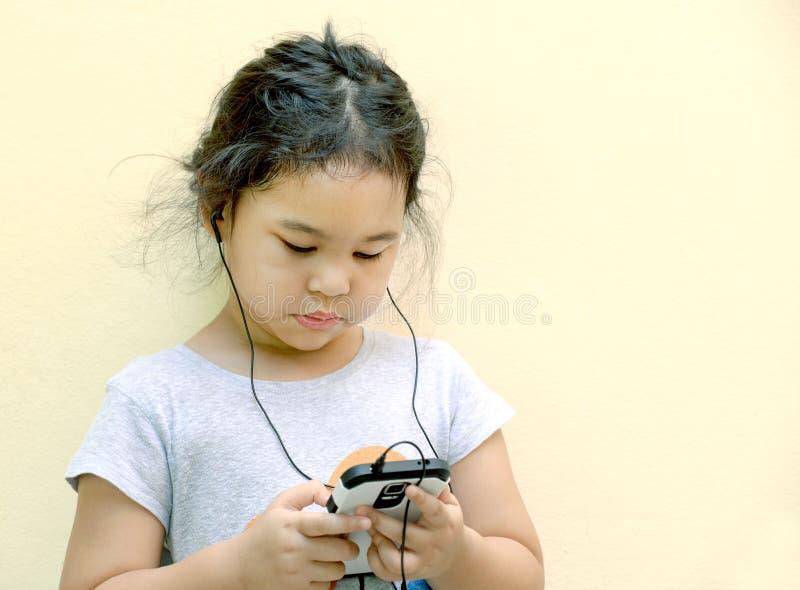 Het meisje luistert muziek met een MP3 speler stock fotografie