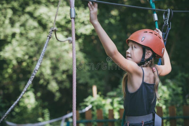 Het meisje maakt het beklimmen in het avonturenpark stock afbeelding
