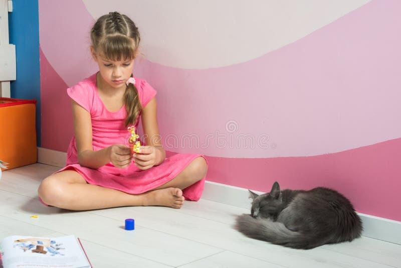 Het meisje maakt berekent van gekleurd document, dichtbij slaapt een binnenlandse kat stock foto's