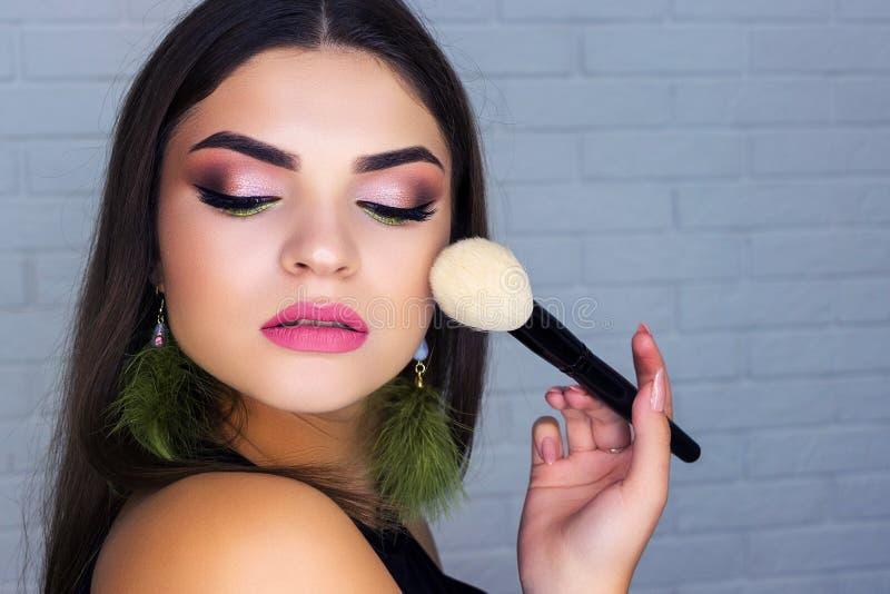 Het meisje maakt de borstel van het make-upgezicht voor make-up stock fotografie