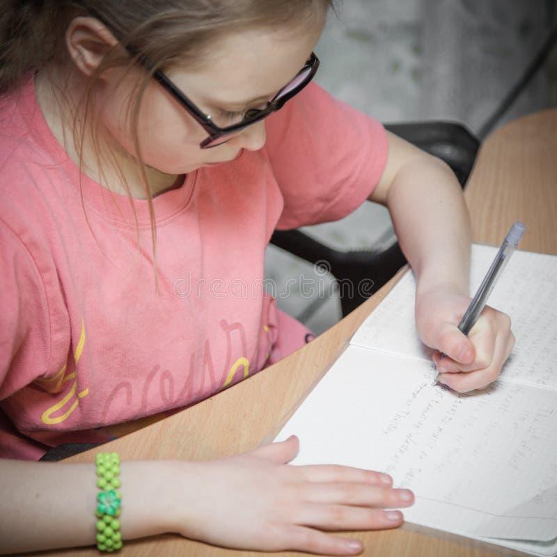 Het meisje maakt geschreven lessen royalty-vrije stock afbeeldingen