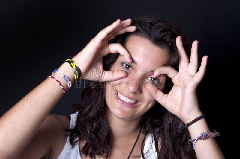 Het meisje maakt glazen van haar vingers. royalty-vrije stock afbeeldingen