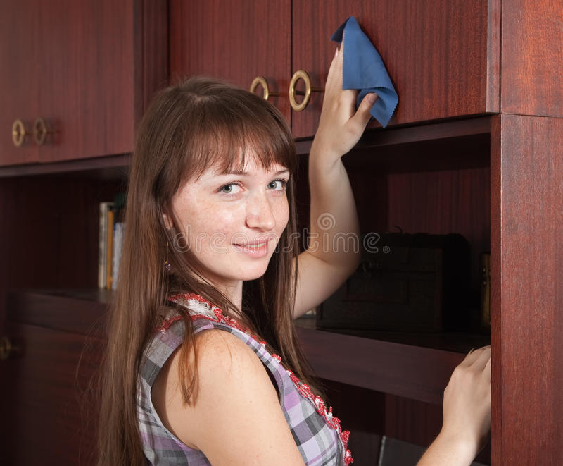 Het meisje maakt meubilair schoon binnen stock fotografie