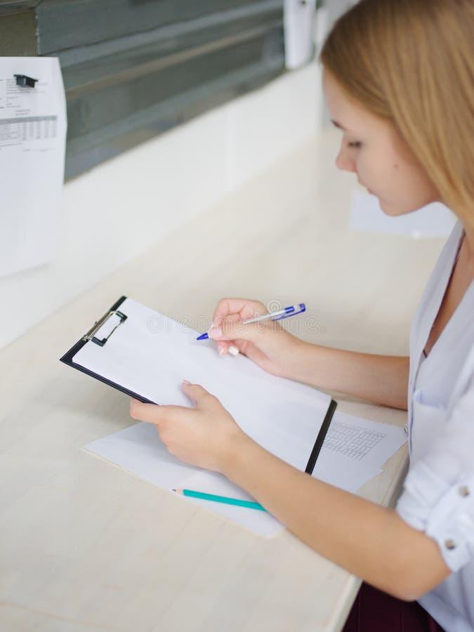 Het meisje maakt nota's op het kantoor royalty-vrije stock fotografie