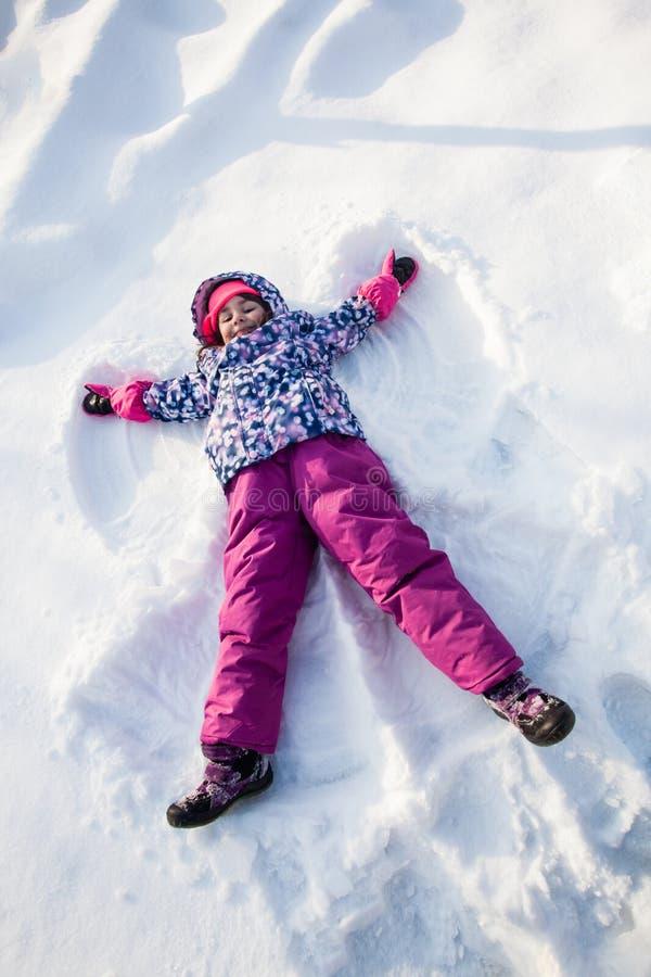 Het meisje maakt sneeuwengel royalty-vrije stock afbeeldingen