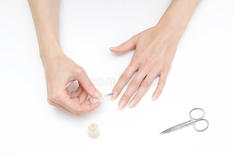 Het meisje maakt tot een manicure beige lak royalty-vrije stock foto