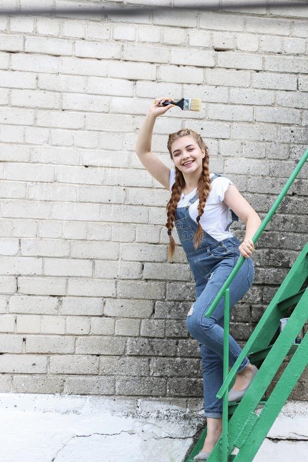 Het meisje maakt het voorbereidingen treffen voor het schilderen van een houten oppervlaktegazebo, omheining stock foto