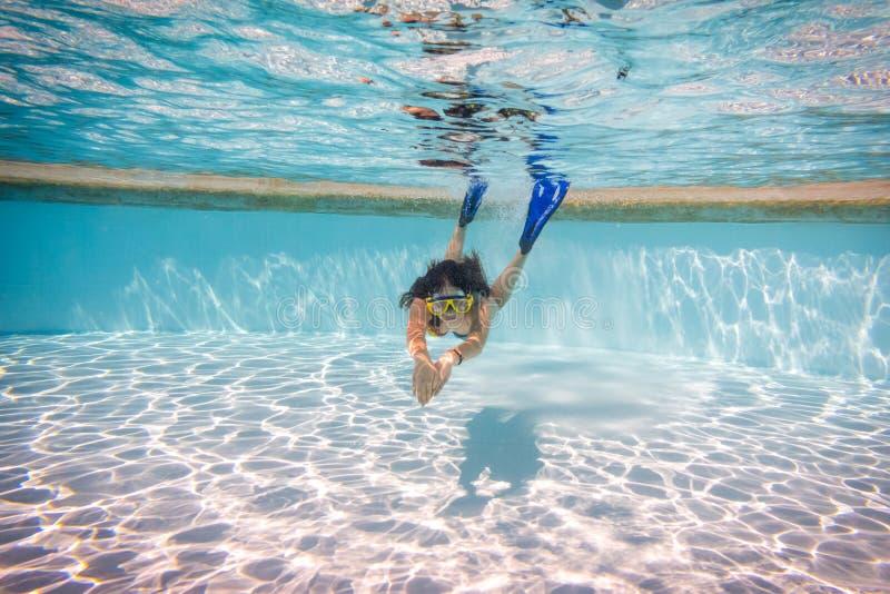 Het meisje in masker duikt in zwembad royalty-vrije stock foto
