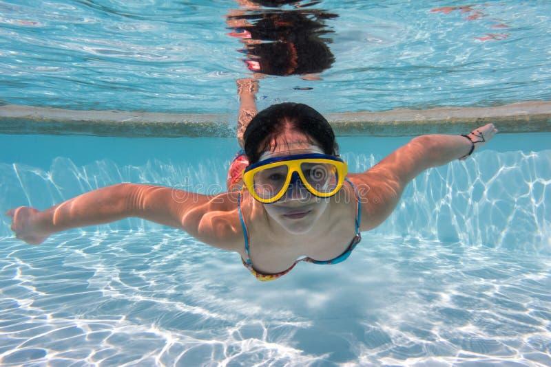 Het meisje in masker duikt in zwembad stock afbeelding