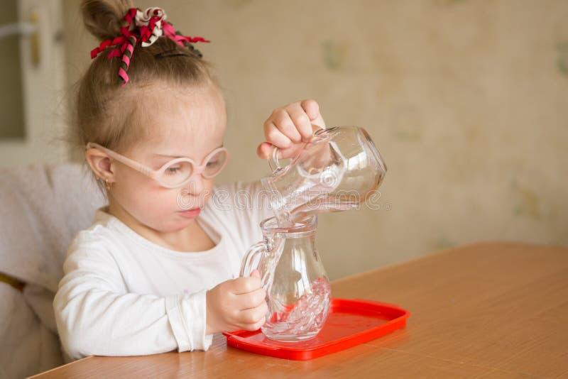 Het meisje met Benedensyndroom giet zacht water van een kruik in een kruik stock foto's
