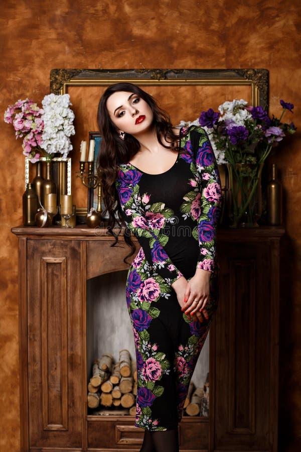 Het meisje met bloemen bevindt zich dichtbij de open haard royalty-vrije stock afbeeldingen