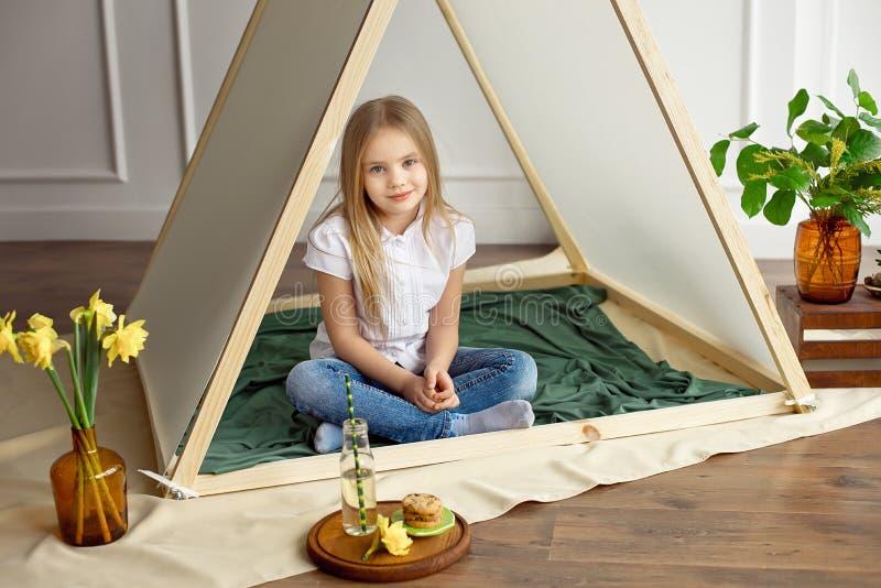 Het meisje met blond haar in een wit overhemd en jeans glimlacht zitting in een tent in de ruimte van de kinderen royalty-vrije stock afbeeldingen