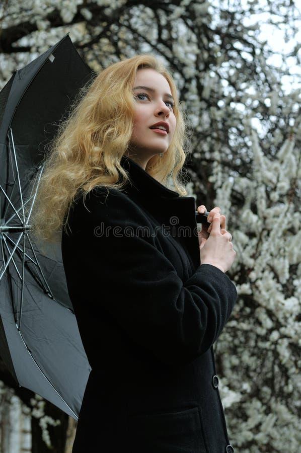 Het meisje met blond haar gekleed in een zwarte laag bevindt zich onder a royalty-vrije stock afbeelding