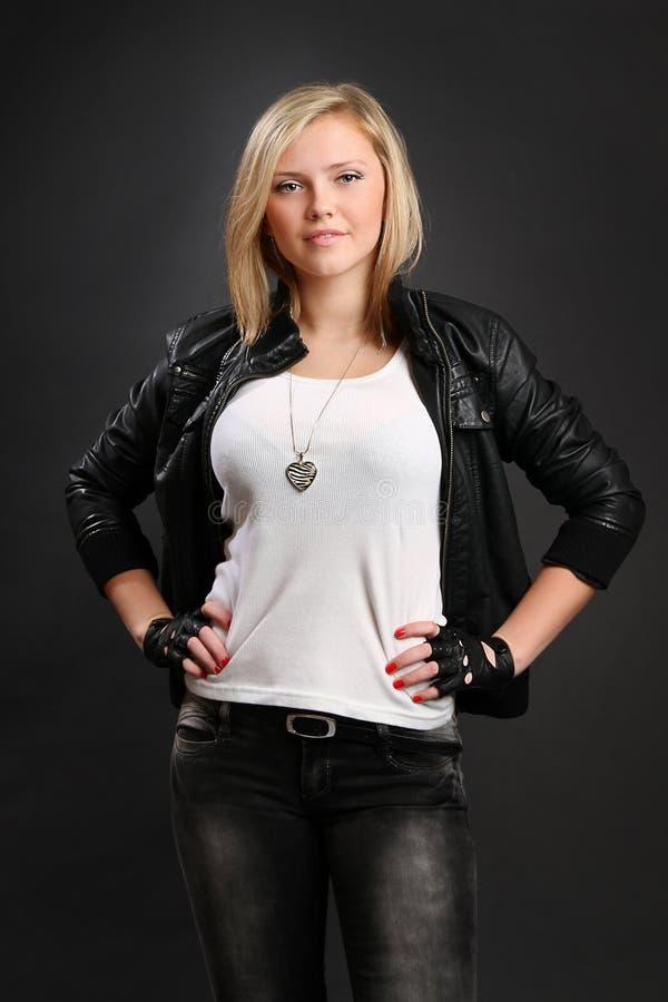 Het meisje met blond haar kleedde zich in zwarte leahter royalty-vrije stock afbeelding