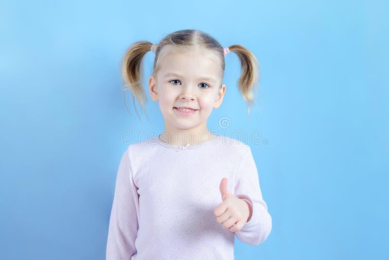 Het meisje met blond haar toont een super gebaar Foto van een vrolijk kind op een blauwe achtergrond royalty-vrije stock fotografie