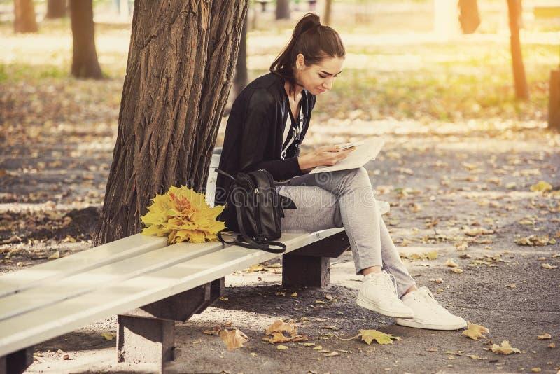 Het meisje met boekzitting onder de boom royalty-vrije stock foto