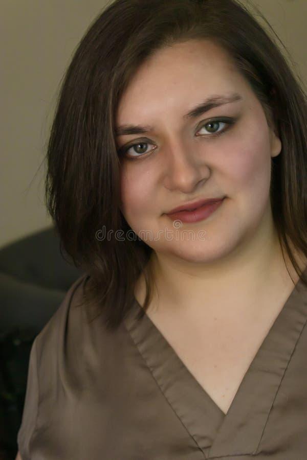 Het meisje met bruin haar ziet vooruit en grijnst stock afbeelding