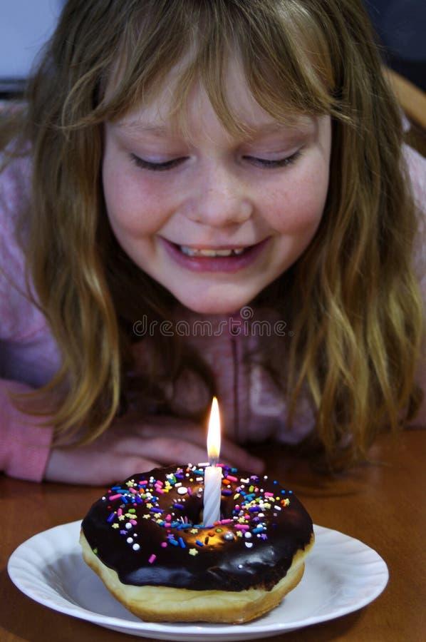 Het meisje met chocoladedoughnut met bestrooit en verjaardagskaars stock afbeelding