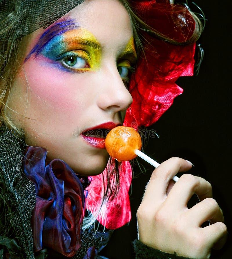 Het meisje met met creatieve samenstelling houdt lolly royalty-vrije stock afbeeldingen