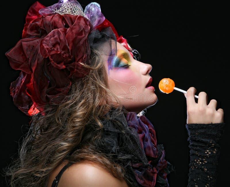 Het meisje met met creatieve samenstelling houdt lolly stock afbeelding