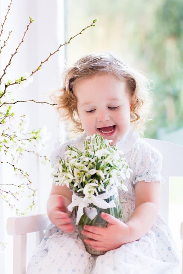 Het meisje met de eerste lente bloeit thuis stock foto