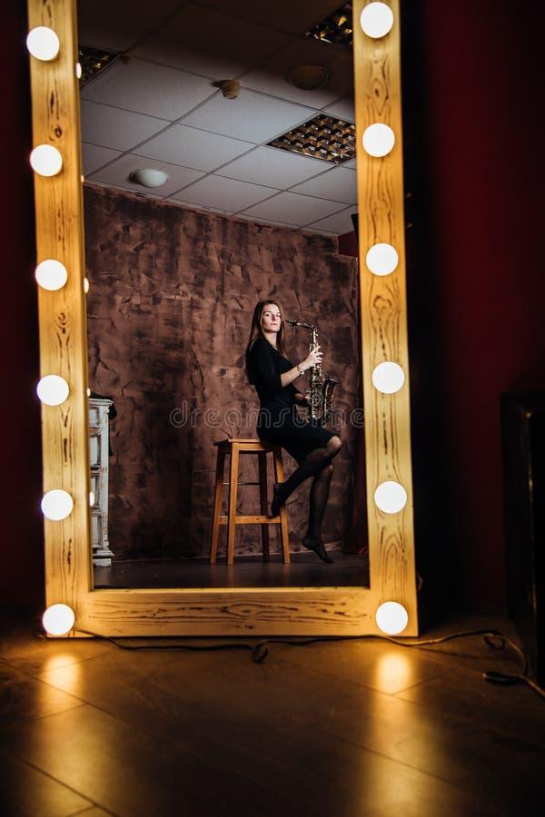 Het meisje met de saxofoon in de spiegel in een zwarte kleding royalty-vrije stock afbeeldingen