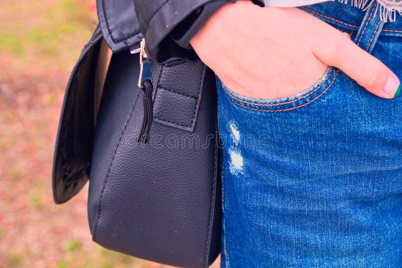 Het meisje met dient jeanszak met zwarte handtas in royalty-vrije stock afbeeldingen