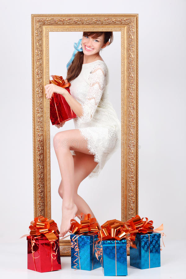 Het meisje met doos met gift komt uit verguld frame royalty-vrije stock fotografie