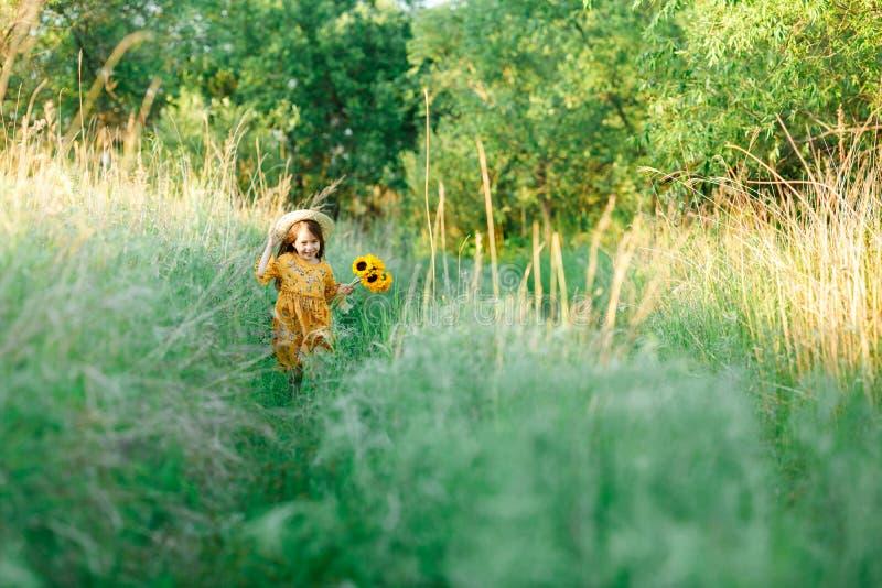 Het meisje met een boeket van wilde gele bloemen loopt in de dag van de weide zonnige zomer in een strohoed De ruimte van het exe royalty-vrije stock afbeeldingen
