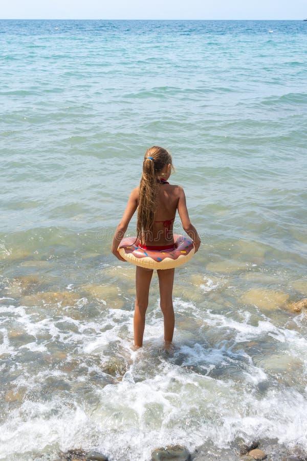 Het meisje met een cirkel gaat zwemmend in het overzees royalty-vrije stock afbeeldingen