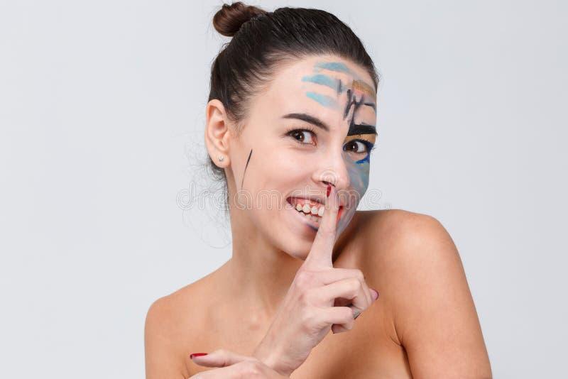 Het meisje met een glimlach hief haar wijsvinger aan haar lippen op een grijze achtergrond op royalty-vrije stock fotografie