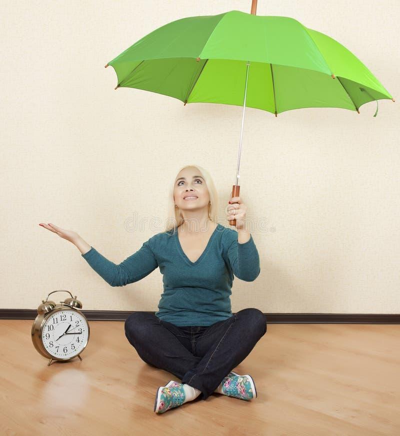 Het meisje met een groene paraplu zit op de vloer naast grote klok royalty-vrije stock afbeeldingen
