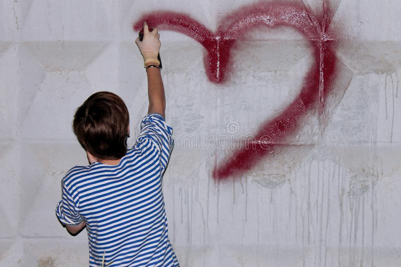 Het meisje met een kort kapsel, trekt graffiti royalty-vrije stock afbeelding