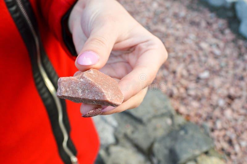 het meisje met een mooie manicure houdt ter beschikking een rode steen, gr. royalty-vrije stock fotografie