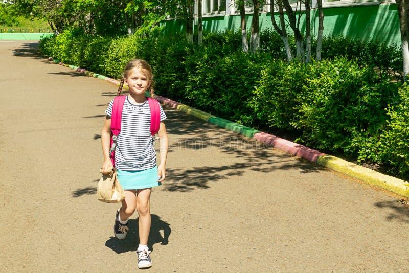 Het meisje met een roze rugzak en een document zak met een beet gaat naar school Het concept van de school Horizontaal kader stock afbeelding