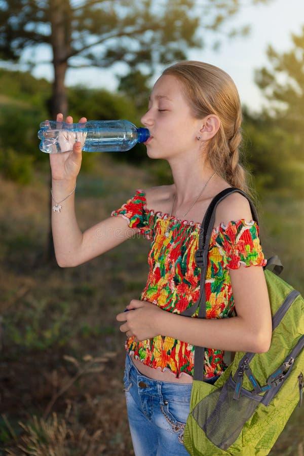 Het meisje met een rugzak drinkt water van een fles, gesloten ogen, rust in het bos, levensstijl stock fotografie
