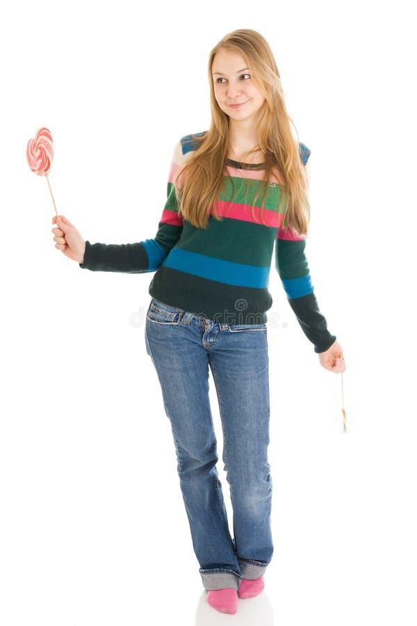 Het meisje met een suikersuikergoed dat op een wit wordt geïsoleerd stock afbeelding
