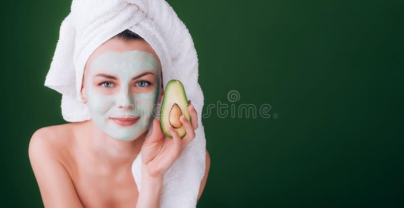 Het meisje met een witte handdoek op haar hoofd met een voedzaam groen masker op haar gezicht en een avocado in haar handen op ee stock foto