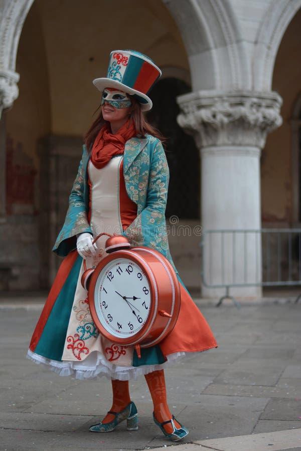 Het meisje met een zonderling kleurrijk kostuum en een reuzewekker stock foto