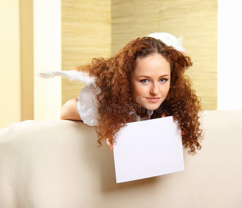 Het meisje met engelenvleugels houdt een leeg wit royalty-vrije stock fotografie