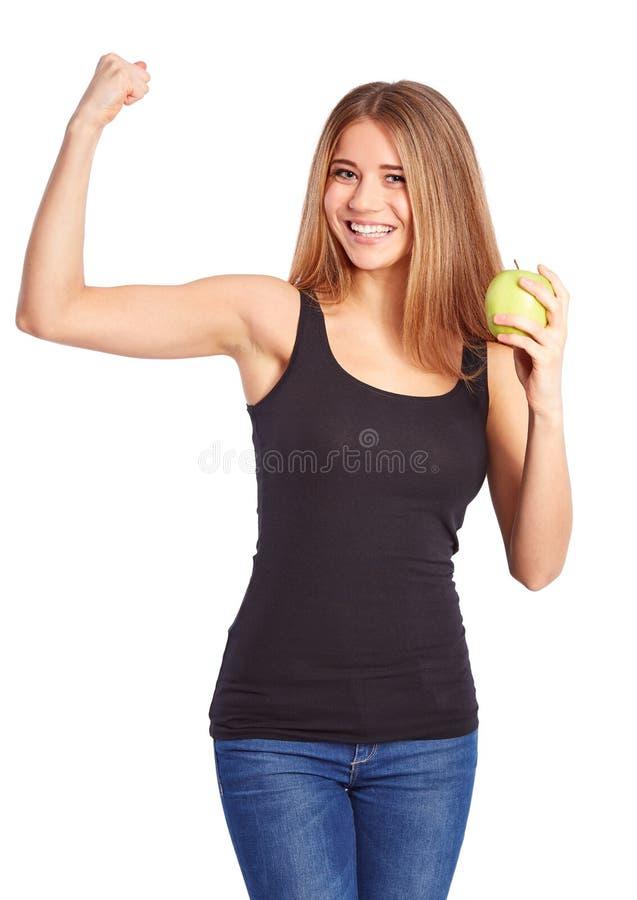 Het meisje met groene appel maakt een gebaar van kracht royalty-vrije stock afbeeldingen